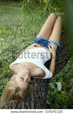 portrait of a young sad girl lying on a tree - stock photo