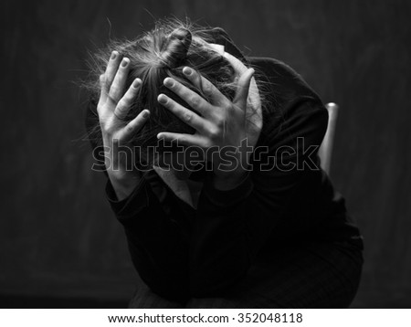 Portrait of a young sad woman , head is put down,  hands are clasping the head, image on a gray background - stock photo