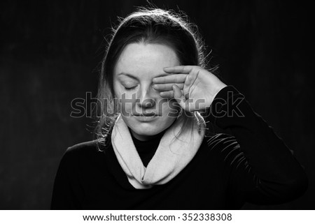Portrait of a young sad woman ,one eye is closed by the hand, grey background - stock photo