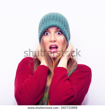 Portrait of a young scared woman.Shocked Girl.Beautiful Blonde Caucasian woman looking surprised and scared - funny. Isolated on white background.Wearing green hat ,scarf and red sweater. - stock photo