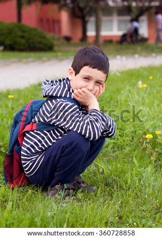 Portrait of a young school boy or preschooler in front of a institutional building. child is looking sad or worried.