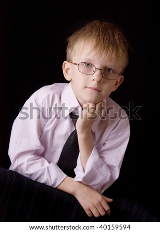 Portrait of a young serious businessman on black background
