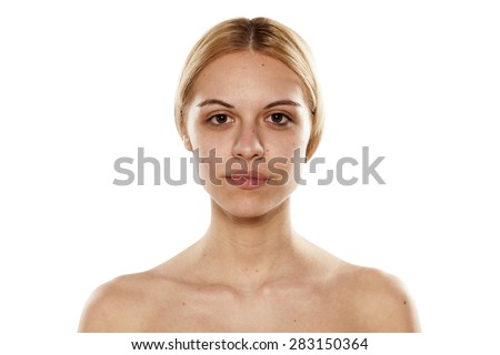 portrait of a young serious woman without makeup on a white background - stock photo