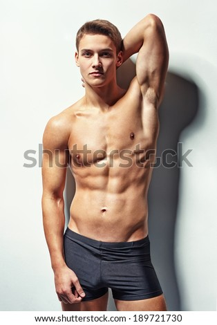Portrait of a young sexy muscular male model in underwear against white wall in sensual pose his hand behind his head - stock photo