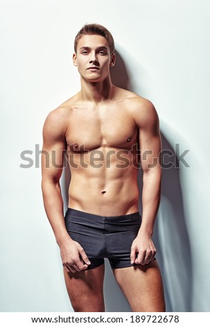 Portrait of a young sexy muscular man in underwear against white wall - stock photo