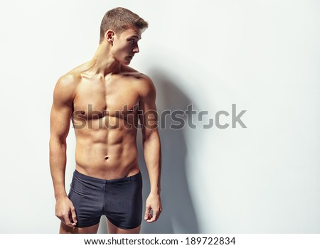 Portrait of a young sexy muscular man in underwear looking away against white wall with copy space - stock photo