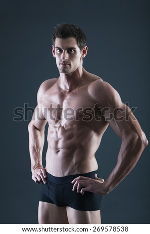 Portrait of a young sexy shirtless muscular man in black underwear - stock photo