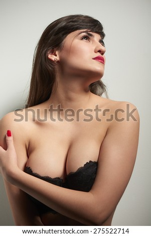 Portrait of a young sexy woman in lingerie looking away out of frame - stock photo