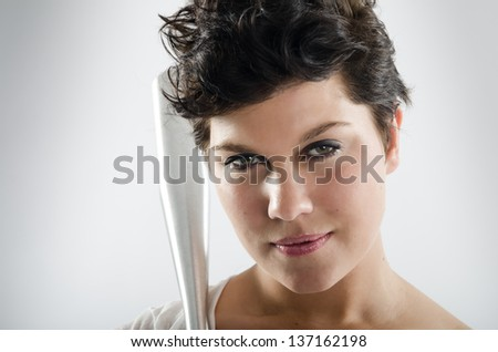 Portrait of a young sexy woman with a baseball bat next to her face - stock photo