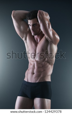 Portrait of a young shirtless muscular man in black underwear - stock photo