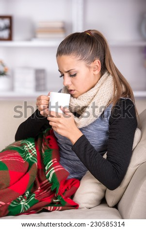 Portrait of a young sick woman who drinks hot tea. - stock photo