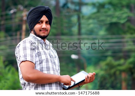 portrait of a young Sikh with tablet in India - stock photo