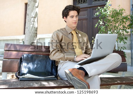 Portrait of a young smart businessman sitting on a wooden bench in the city and using his laptop computer, outdoors.
