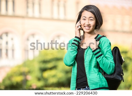 Portrait of a young smiling asian student with university building in the background. She is saying by phone. - stock photo