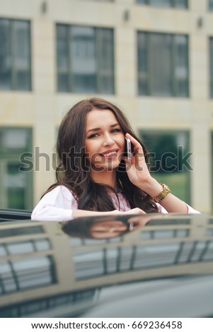Portrait of a young smiling beautiful brunette business woman in a pink dress who stands near a car and talks on her mobile phone