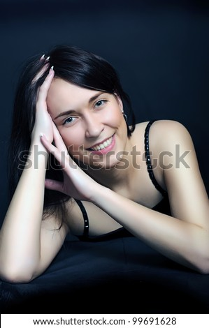 portrait of a young smiling brunette  woman with arms crossed under her hair on dark black background - stock photo