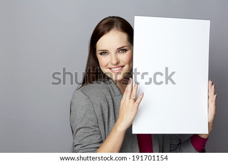 Portrait of a young smiling business woman with long brunette hair on gray studio background holding a blank white poster or an empty page with space for text - stock photo