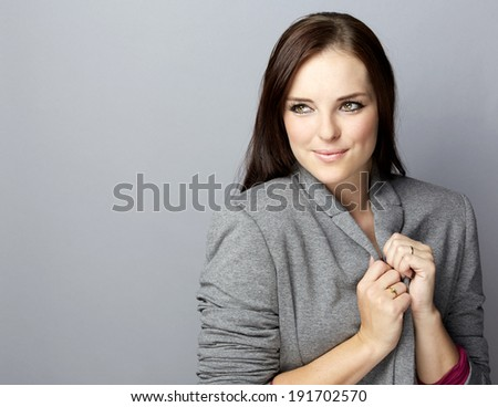 Portrait of a young smiling business woman with long brunette hair on gray studio background, wearing grey corporate blazer jacket  - stock photo