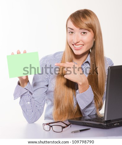 Portrait of a young smiling businesswoman holding a blank card near laptop isolated on white. - stock photo