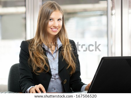 Portrait of a young smiling businesswoman using her computer - stock photo