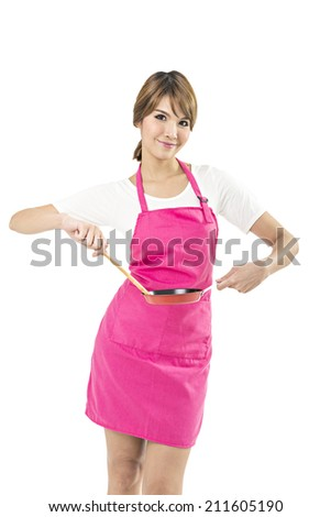 portrait of a young smiling caucasian female teen dressed in apron, holding a frying pan in front of her, on white.  - stock photo