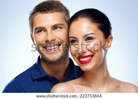 Portrait of a young smiling couple on blue background - stock photo