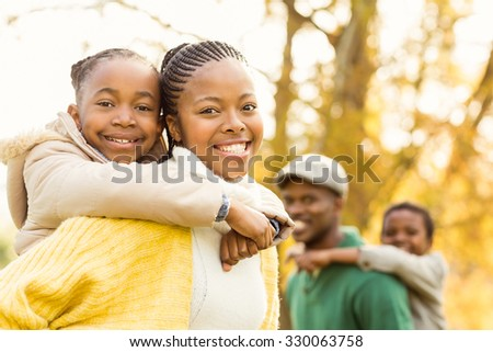 Portrait of a young smiling family in piggyback on an autumns day - stock photo