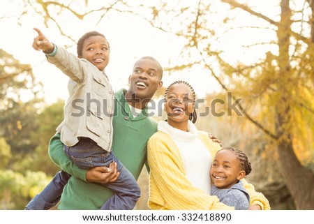 Portrait of a young smiling family pointing something on an autumns day