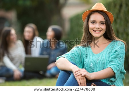 Portrait of a young, smiling female student, with blurred students are sitting in the park. She is looking at the camera. - stock photo