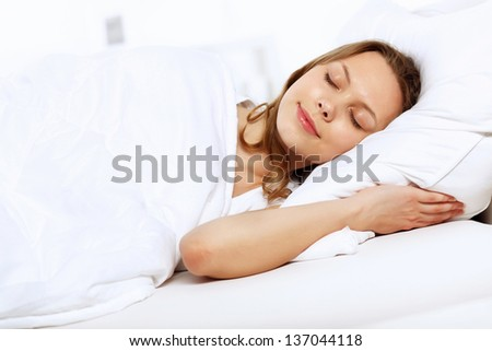 Portrait of a young smiling girl in bed - stock photo