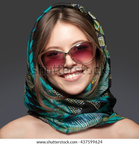 Portrait of a young smiling girl in sunglasses and a green scarf. Studio, gray background. - stock photo