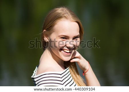 Portrait of a young smiling girl on the blurry background of greenery. Beautiful woman in a striped dress - stock photo