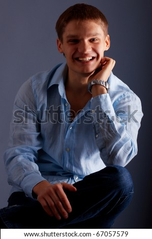 Portrait of a young smiling man looking to camera - stock photo