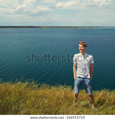 Portrait of a young smiling man on nature background. good looking man summer outdoors
