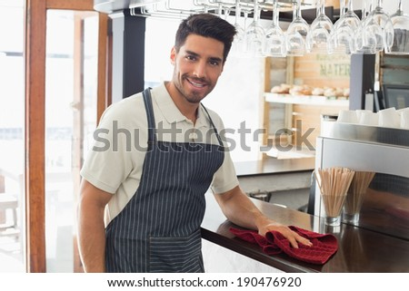 Portrait of a young smiling waiter cleaning countertop with sponge - stock photo