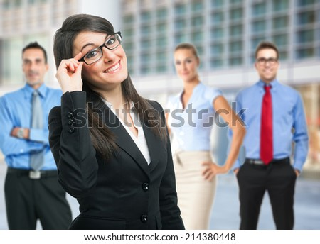 Portrait of a young smiling woman holding her eyeglasses - stock photo