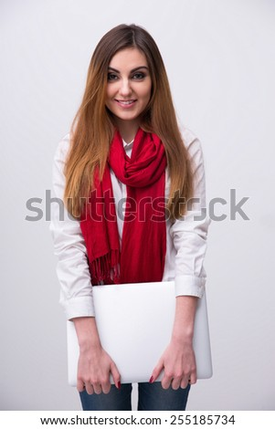 Portrait of a young smiling woman in red scarf with laptop - stock photo