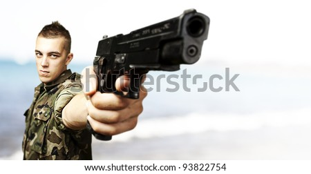 portrait of a young soldier aiming with a gun against a beach background - stock photo