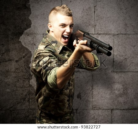 portrait of a young soldier aiming with a shotgun against a grunge background - stock photo
