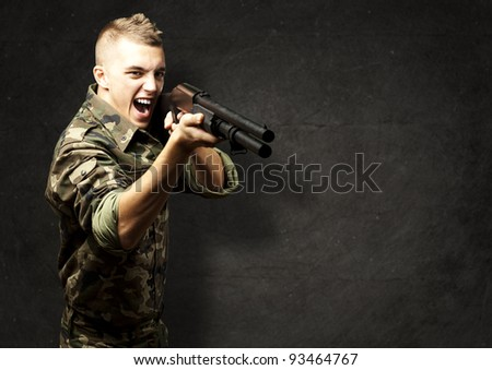portrait of a young soldier aiming with shotgun against a grunge background - stock photo