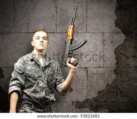 portrait of a young soldier holding a rifle wearing an urban camouflage against a grunge brick wall - stock photo
