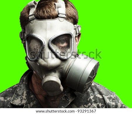portrait of a young soldier wearing a gas mask against a removable chroma key background