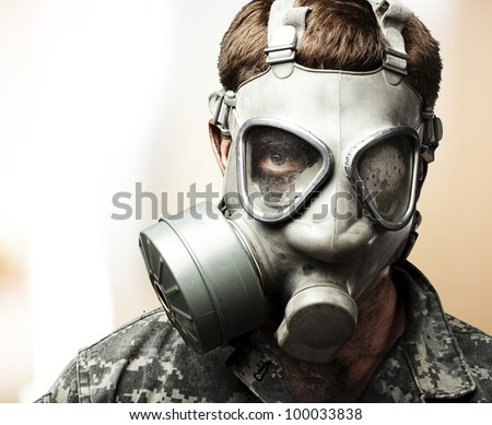 portrait of a young soldier wearing a gas mask against an abstract background