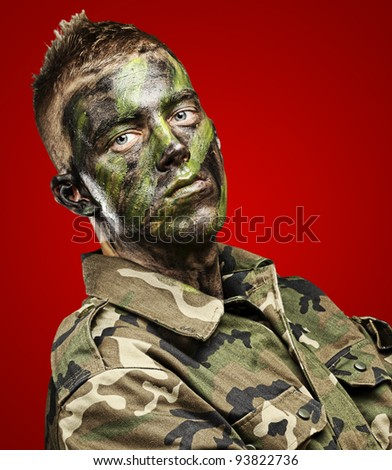 portrait of a young soldier with a jungle camouflage paint on a red background