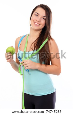 Portrait of a young sport woman holding apple and measuring tape over white background