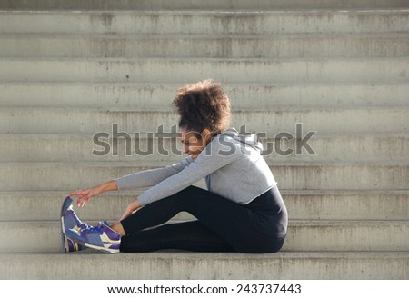 Portrait of a young sports woman sitting on stairs stretching leg muscles