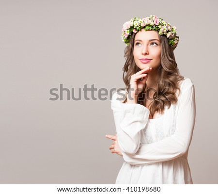 Portrait of  a young spring beauty wearing flower wreath. - stock photo