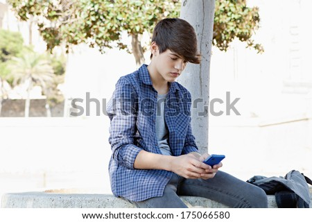 Portrait of a young student teenager boy sitting by a tree in a college campus using a smartphone mobile to network and browse the internet during a sunny day. Technology outdoors. - stock photo