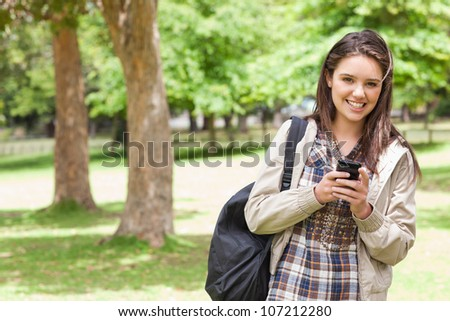 Portrait of a young student using a smartphone in a park - stock photo