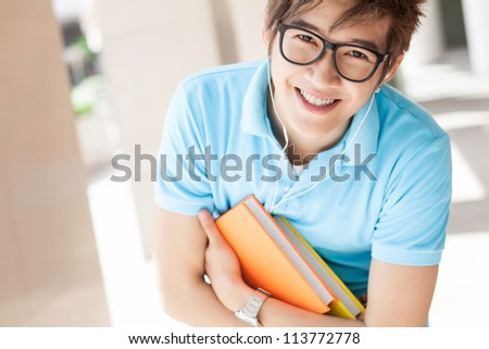 Portrait of a young student with textbooks looking at camera - stock photo